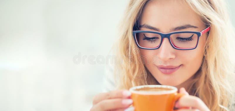 Φλιτζάνι του καφέ υπό εξέταση της ευτυχούς νέας γυναίκας στοκ φωτογραφίες