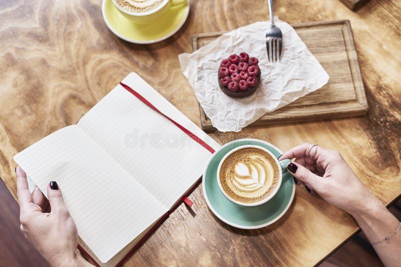 Φλιτζάνι του καφέ latte και γλυκιά ζύμη στον ξύλινο πίνακα στα χέρια γυναικών ανοιγμένο βιβλίο σημειώσεων χεριών λαβή, διάστημα γ στοκ φωτογραφία