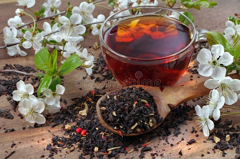 Φλιτζάνι τσάι και λουλούδια sakura ξηρό τσάι φύλλα σε κουτάλι σε ξύλινο τραπέζι στοκ εικόνες με δικαίωμα ελεύθερης χρήσης