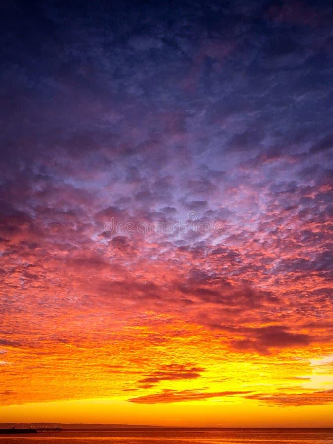 Φλογερό πορτοκαλί και πορφυρό ηλιοβασίλεμα στο νεφελώδη ουρανό στοκ φωτογραφία με δικαίωμα ελεύθερης χρήσης