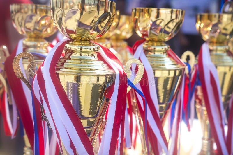 Φλυτζάνια και μετάλλια αθλητικών βραβείων στους ανταγωνισμούς Τα βραβεία που απονέμονται τους πρωτοπόρους των αθλητικών ανταγωνισ στοκ φωτογραφίες