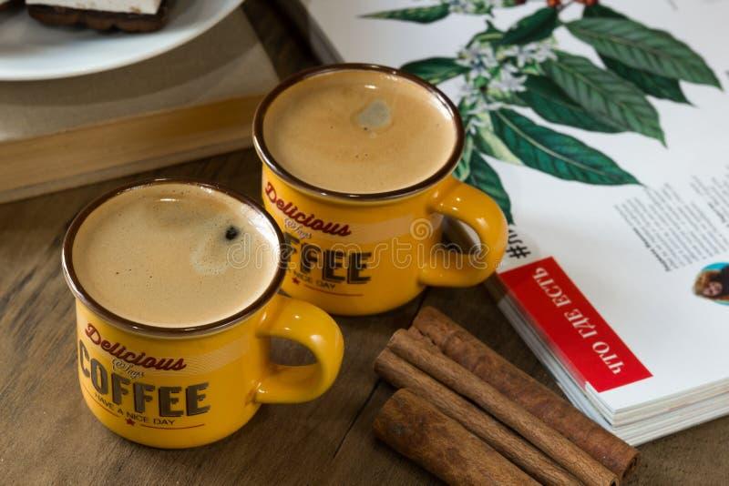 Φλυτζάνια με το αρωματικό espresso σε έναν ξύλινο πίνακα, κεραμικά πιατικά, με ένα πιάτο των μπισκότων και της κανέλας τσιπ σοκολ στοκ φωτογραφίες