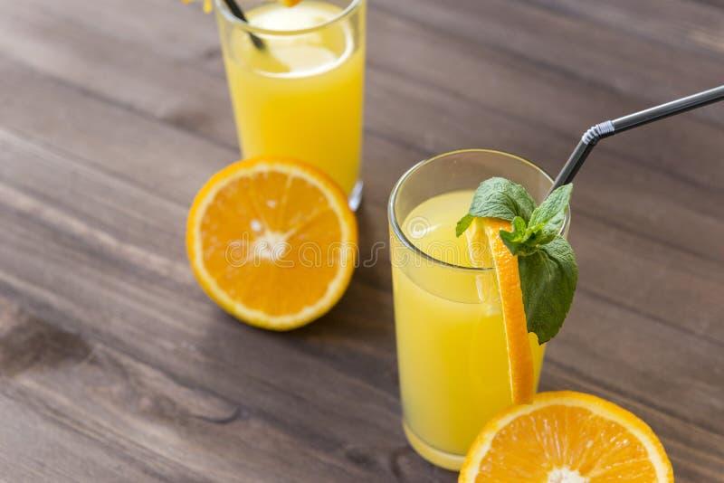 φλυτζάνια του χυμού από πορτοκάλι με ένα άχυρο, κλαδάκι της μέντας, μισό φρέσκο πορτοκάλι σε ένα καφετί ξύλινο υπόβαθρο στοκ εικόνες