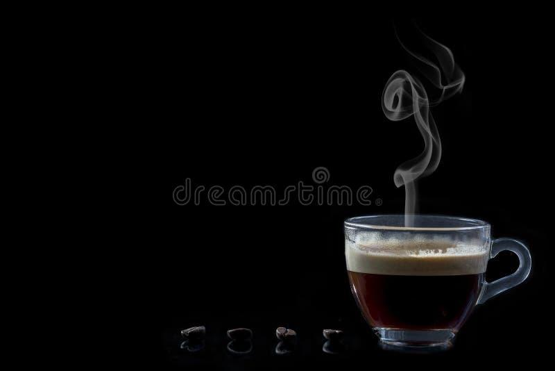 Φλυτζάνι γυαλιού του βρασίματος στον ατμό του καφέ και των ψημένων φασολιών στο μαύρο υπόβαθρο στοκ εικόνες