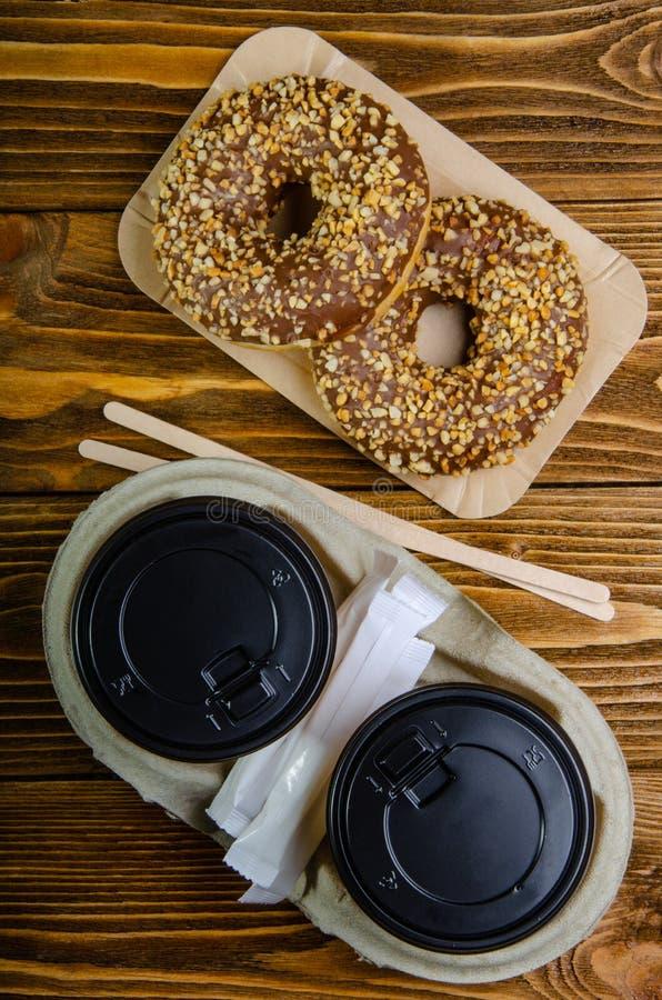 Φλυτζάνι εγγράφου για τον καφέ, μίας χρήσης οικολογικές προμήθειες καφέ Donuts στους δίσκους εγγράφου Ξύλινος πίνακας στοκ εικόνα