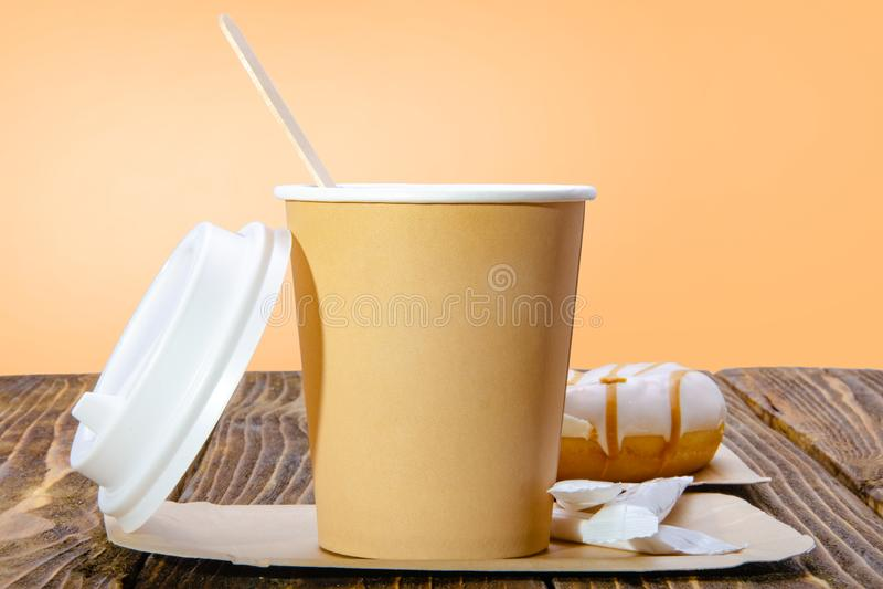 Φλυτζάνι εγγράφου για τον καφέ Πορτοκαλί υπόβαθρο στοκ εικόνες