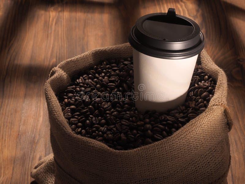 Φλυτζάνι εγγράφου καφέ sackcloth στην τσάντα στο ξύλινο υπόβαθρο στοκ εικόνες