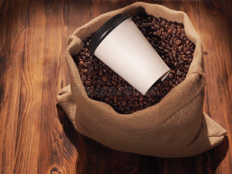 Φλυτζάνι εγγράφου καφέ sackcloth στην τσάντα στο ξύλινο υπόβαθρο στοκ φωτογραφία