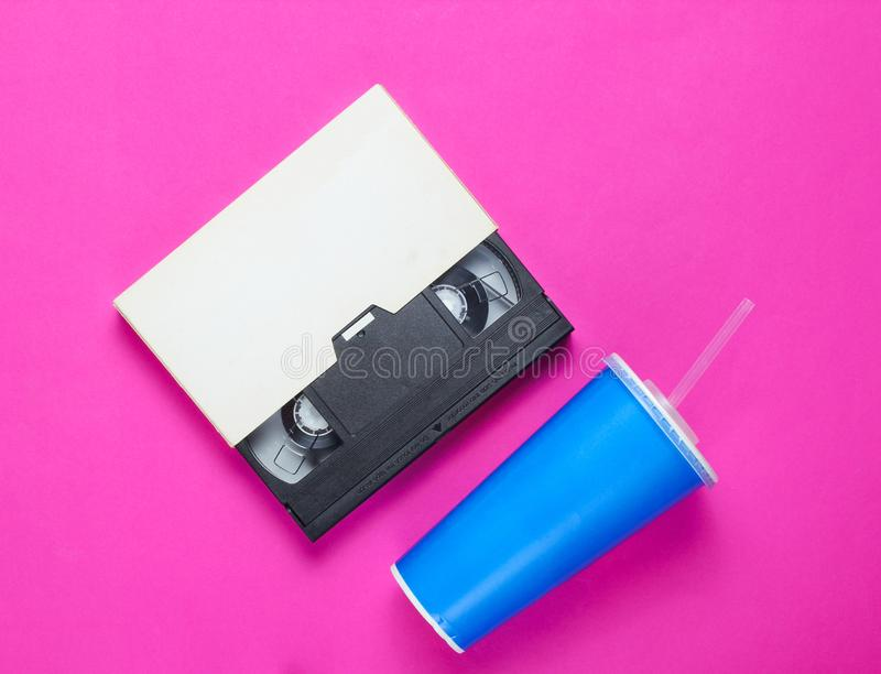 Φλυτζάνι εγγράφου με το άχυρο, τηλεοπτική κασέτα στο ρόδινο υπόβαθρο Η δεκαετία του '80 κουλτούρα ποπ, αναδρομικό ύφος r στοκ φωτογραφία με δικαίωμα ελεύθερης χρήσης