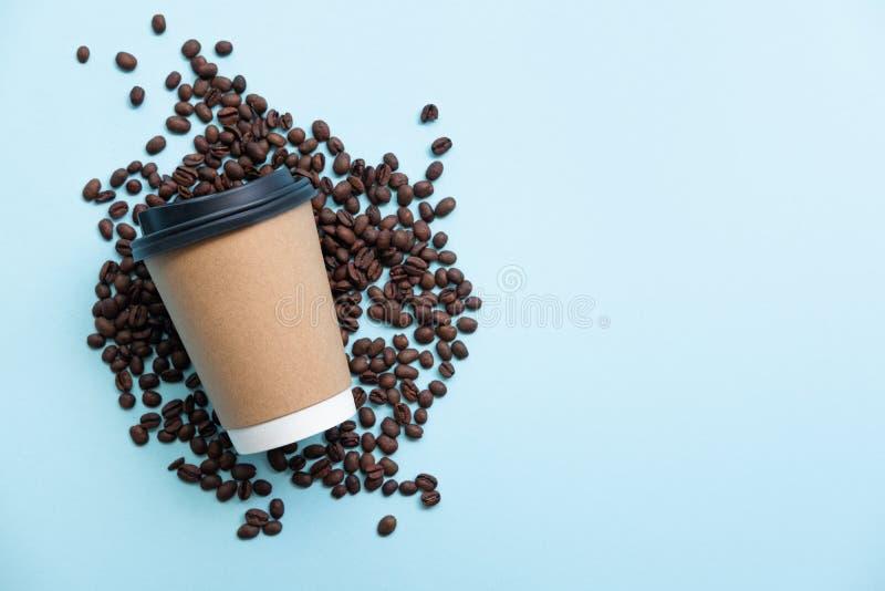 Φλυτζάνι εγγράφου στα διεσπαρμένα φασόλια καφέ o στοκ εικόνα με δικαίωμα ελεύθερης χρήσης