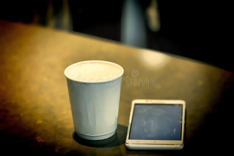 Φλυτζάνι εγγράφου, φλιτζάνι του καφέ, φλυτζάνι του latte, smartphone στον πίνακα στοκ φωτογραφία