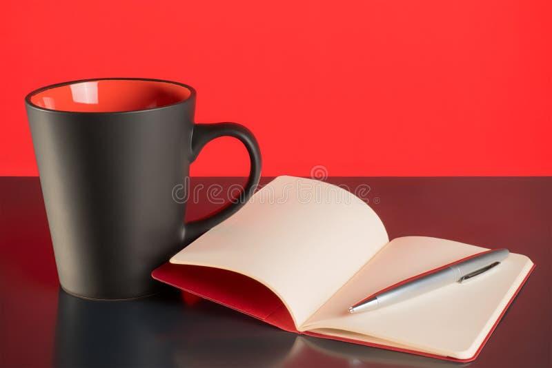 Φλυτζάνι καφέ, ανοικτές σημειωματάριο και μάνδρα στο μαύρο πίνακα στοκ φωτογραφίες με δικαίωμα ελεύθερης χρήσης