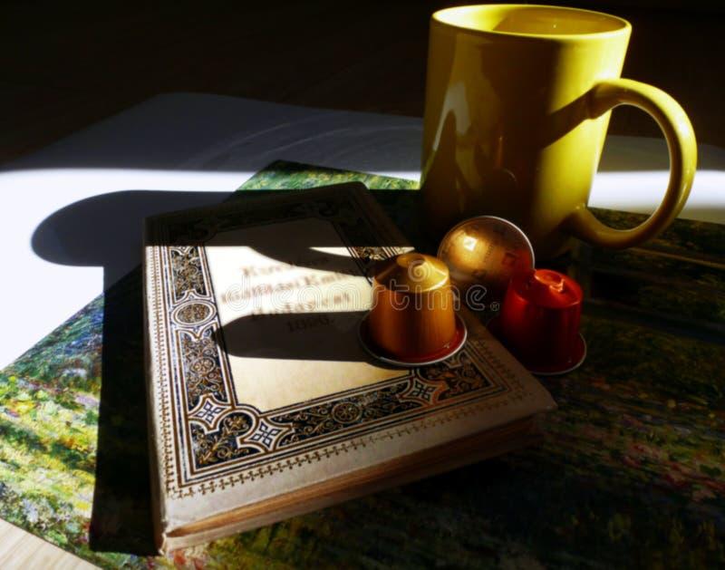 Φλυτζάνι καφέ, κάψες καφέ ένα βιβλίο και σκιές στοκ εικόνες με δικαίωμα ελεύθερης χρήσης