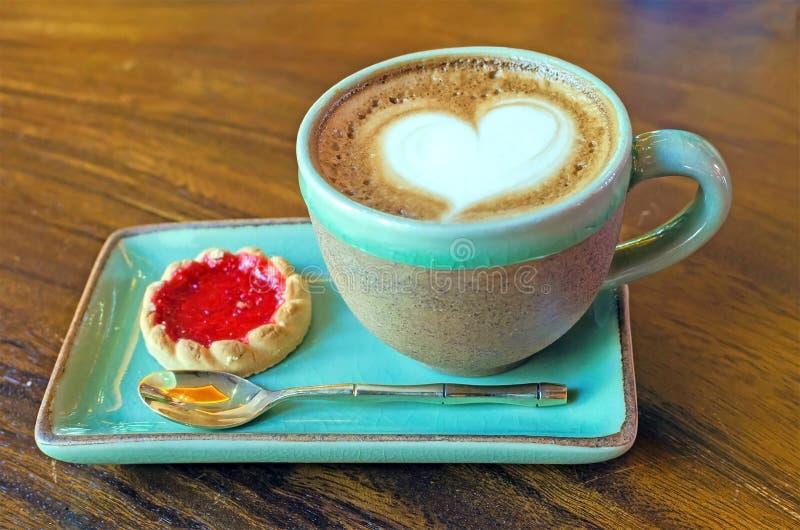 φλυτζάνι καφέ με τη μορφή καρδιών με το μπισκότο φραουλών στο μπλε plat στοκ φωτογραφία με δικαίωμα ελεύθερης χρήσης
