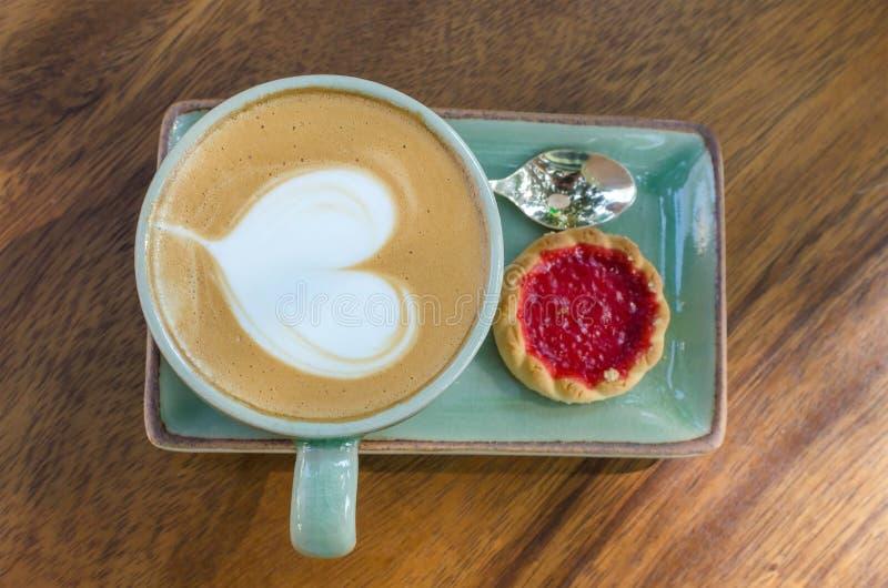 φλυτζάνι καφέ με τη μορφή καρδιών με το μπισκότο φραουλών στο μπλε plat στοκ φωτογραφίες