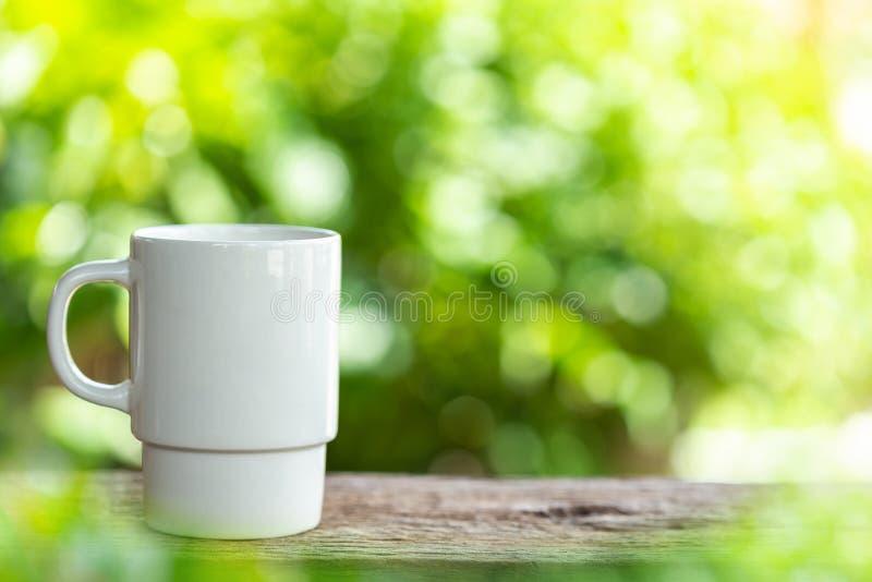 Φλυτζάνι καφέ στον ξύλινο πίνακα ή μετρητής με το πράσινο ελαφρύ BL φύσης στοκ εικόνα με δικαίωμα ελεύθερης χρήσης
