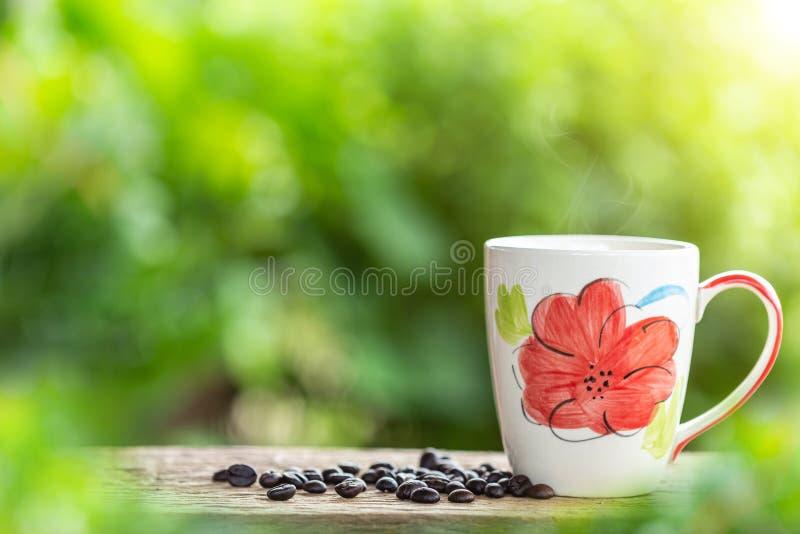 Φλυτζάνι καφέ στον ξύλινο πίνακα ή μετρητής με το πράσινο ελαφρύ BL φύσης στοκ φωτογραφία με δικαίωμα ελεύθερης χρήσης