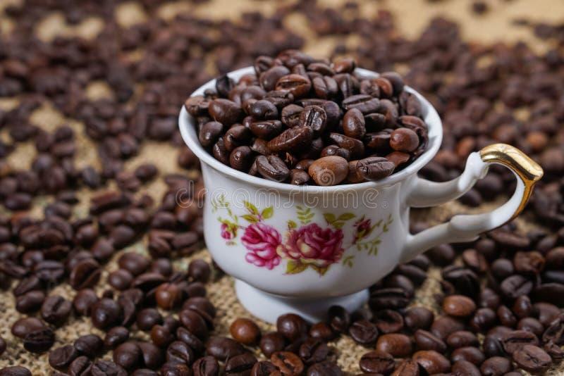 Φλυτζάνι καφέ τα πορφυρά λουλούδια που γεμίζουν με με τα φασόλια στοκ εικόνα