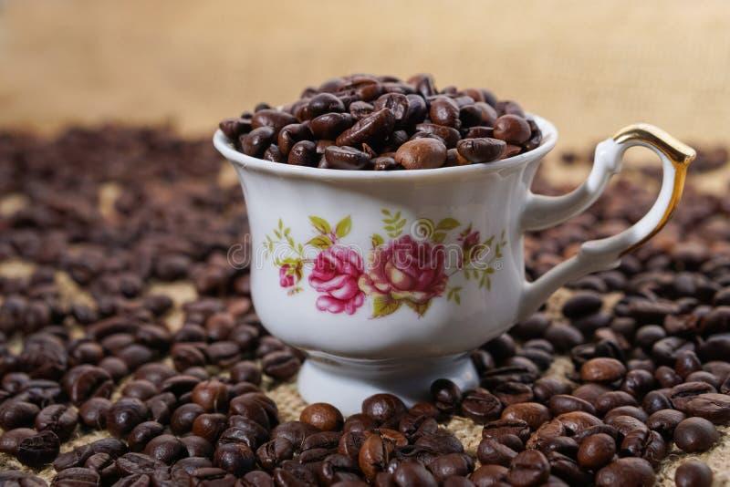Φλυτζάνι καφέ τα πορφυρά λουλούδια που γεμίζουν με με τα φασόλια στοκ εικόνες