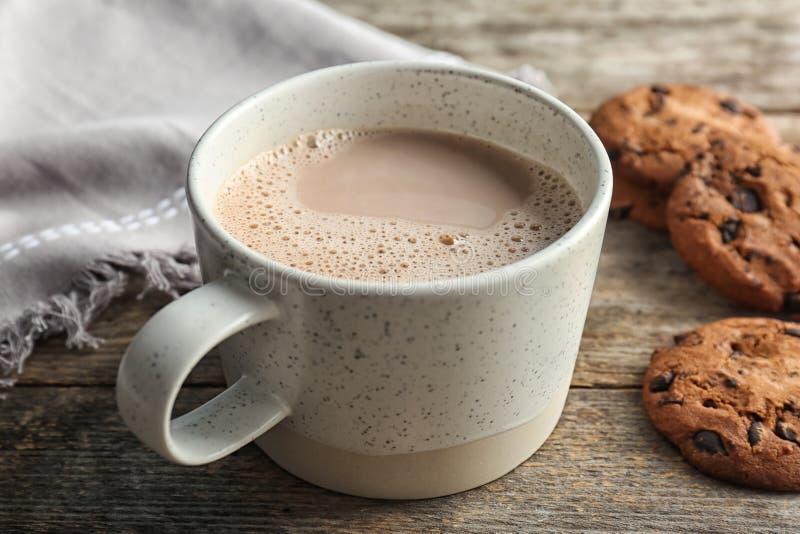Φλυτζάνι με το εύγευστα ζεστά ποτό και τα μπισκότα κακάου στοκ εικόνα