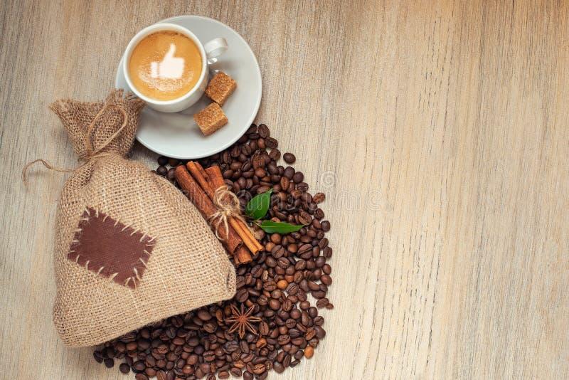 Φλυτζάνι με το espresso με τα φασόλια καφέ, burlap το σάκο και την κανέλα στο ελαφρύ ξύλινο υπόβαθρο Με το ομοειδές σημάδι στον α στοκ εικόνες