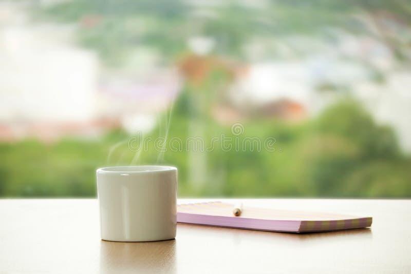 Φλυτζάνι του καυτού καφέ με το βιβλίο μολυβιών και σημειώσεων στον πίνακα στον καφέ στοκ εικόνα με δικαίωμα ελεύθερης χρήσης