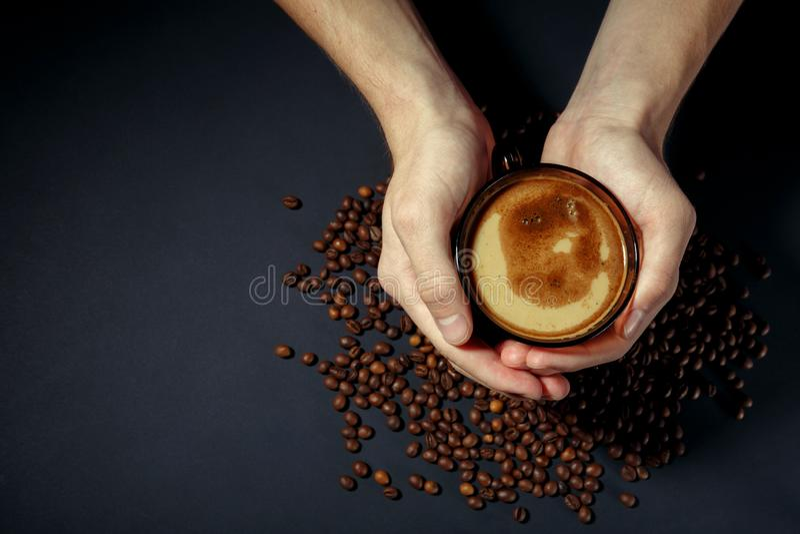 Φλυτζάνι του καυτού καφέ στα χέρια με τα διεσπαρμένα ψημένα σιτάρια στον πίνακα στοκ φωτογραφίες