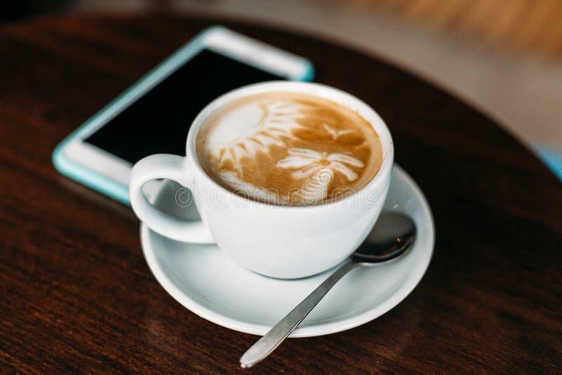 Φλυτζάνι του καυτού καφέ τέχνης latte στον ξύλινο πίνακα στοκ εικόνες