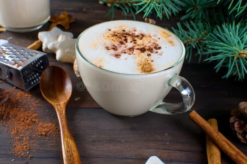 Φλυτζάνι του καυτού καφέ latte, της κανέλας, των μπισκότων και των κλάδων έλατου στοκ φωτογραφία
