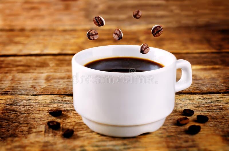 Φλυτζάνι του καυτού μαύρου καφέ με τα φασόλια καφέ στοκ φωτογραφίες