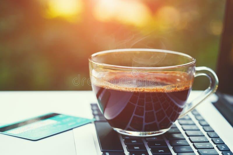 φλυτζάνι του καυτού μαύρου καφέ, της πιστωτικής κάρτας και του ανοικτού lap-top στον ξύλινο πίνακα, ηλιόλουστο πράσινο θολωμένο θ στοκ εικόνες