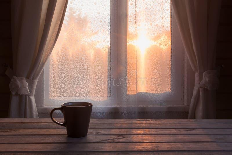 Φλυτζάνι του μαύρου καφέ ή του τσαγιού μπροστά από το παράθυρο στον ξύλινο πίνακα διάστημα αντιγράφων ρωμανικό ηλιοβασίλεμα στοκ εικόνα