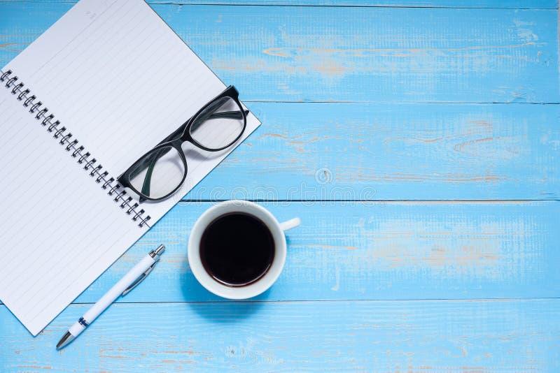 Φλυτζάνι του μαύρου καφέ και του έξυπνου τηλεφώνου με τις προμήθειες γραφείων  γυαλιά μανδρών, σημειωματάριων και ματιών στο ξύλι στοκ φωτογραφία