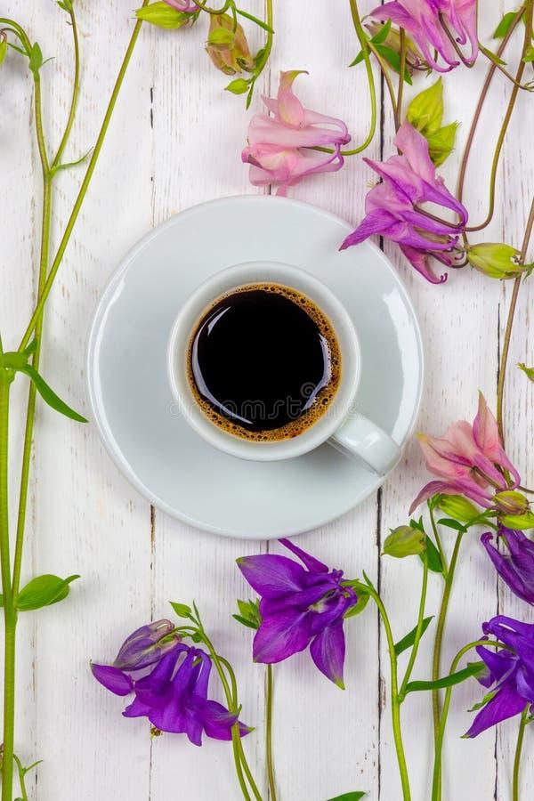 Φλυτζάνι του μαύρου καφέ σε ένα πιατάκι μεταξύ των λουλουδιών σε έναν άσπρο ξύλινο πίνακα, τοπ κινηματογράφηση σε πρώτο πλάνο άπο στοκ εικόνες με δικαίωμα ελεύθερης χρήσης