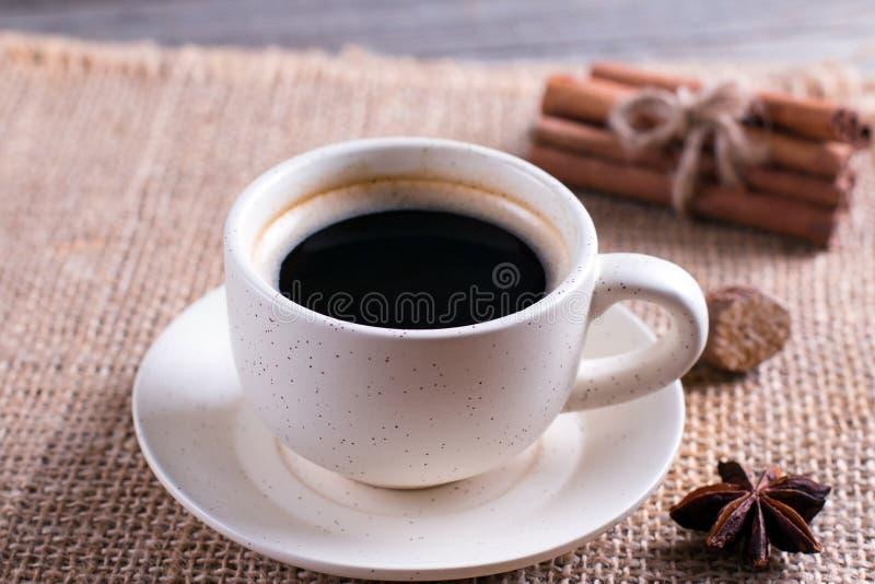 Φλυτζάνι του μαύρου καφέ στο φλυτζάνι, γλυκάνισο αστεριών, ραβδιά κανέλας στον ξύλινο πίνακα στοκ εικόνα