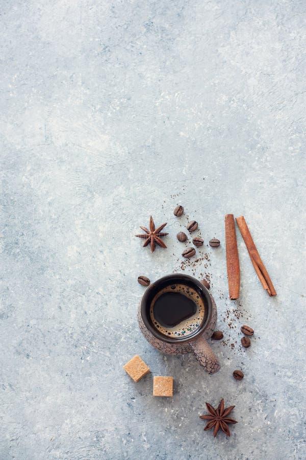 Φλυτζάνι του μαύρου καφέ, των φασολιών καφέ, της καφετιών ζάχαρης και της κανέλας στοκ φωτογραφίες