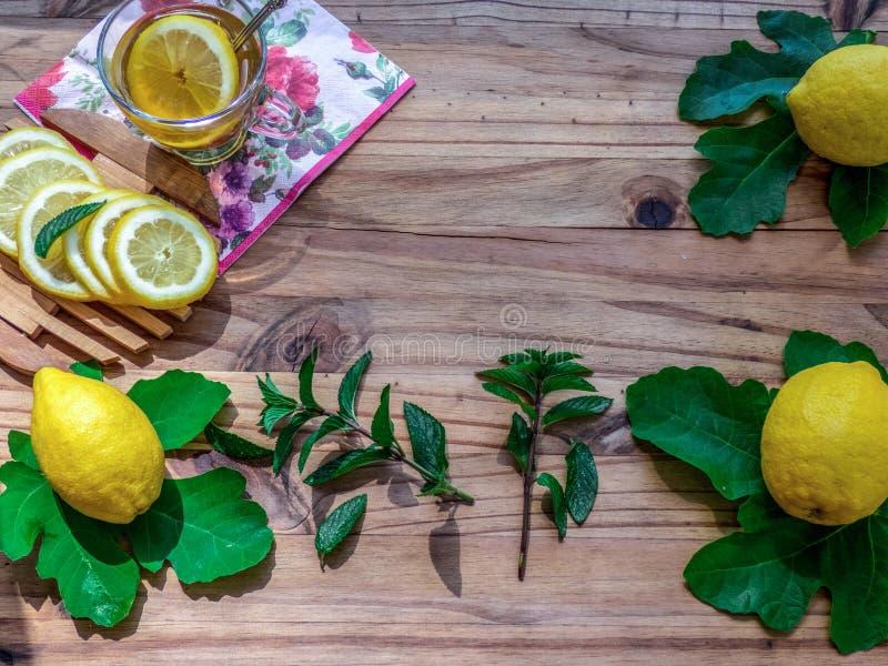 Φλυτζάνι του πράσινου τσαγιού με τα πλήρη και τεμαχισμένα φρέσκα λεμόνια στον ξύλινο πίνακα Μέντα και πράσινα φύλλα στοκ εικόνες
