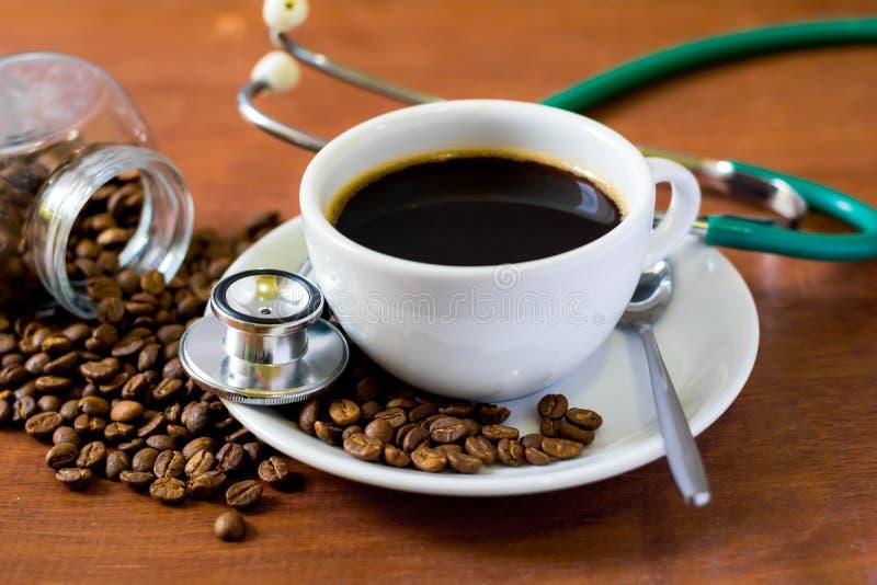 Φλυτζάνι του σκοτεινού καφέ με τα φασόλια καφέ και του στηθοσκοπίου στο ξύλινο υπόβαθρο Έννοια υγείας ποιοι συμπαθούν το ποτό ένα στοκ εικόνα
