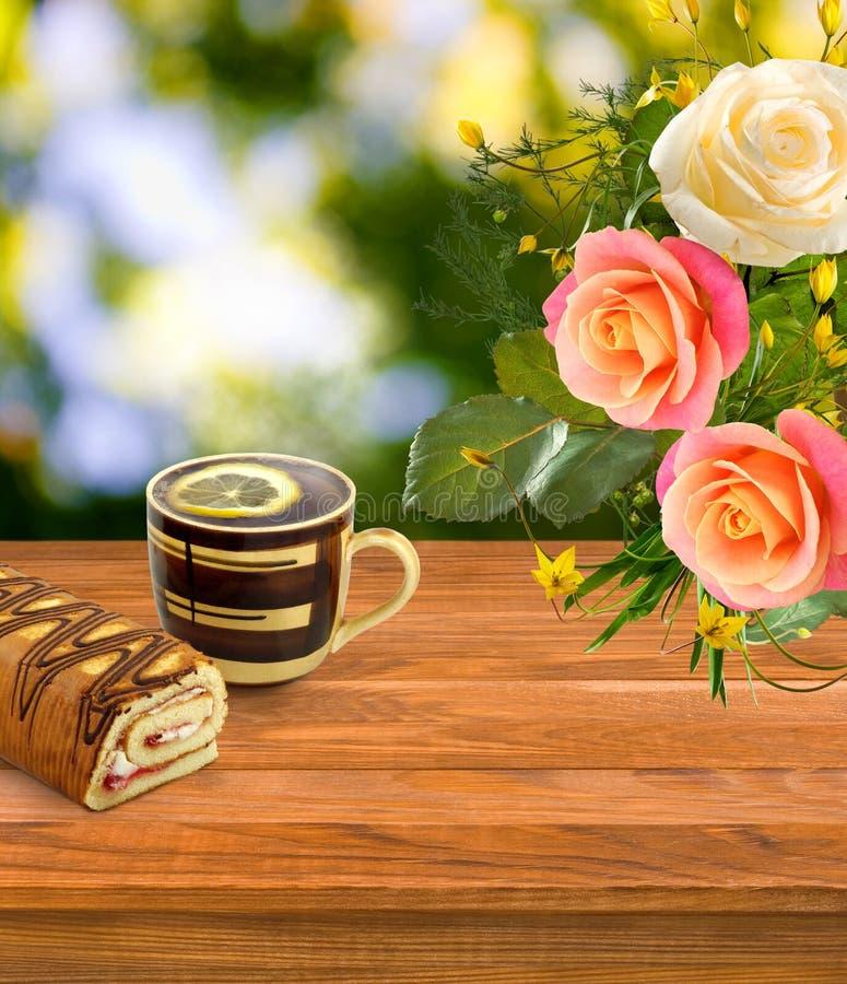 φλυτζάνι του τσαγιού, του γλυκών ρόλου και των λουλουδιών στην επιτραπέζια κινηματογράφηση σε πρώτο πλάνο ελεύθερη απεικόνιση δικαιώματος