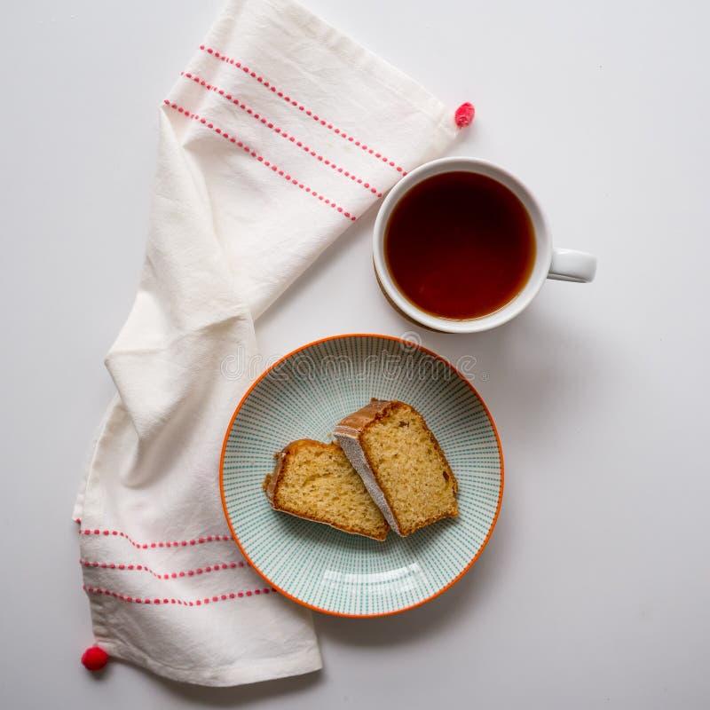 Φλυτζάνι του τσαγιού και δύο φέτες του κέικ σφουγγαριών σε ένα πιάτο σε έναν άσπρο πίνακα με μια άσπρη και κόκκινη πετσέτα τσαγιο στοκ φωτογραφίες