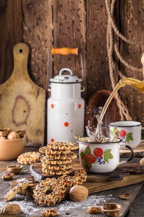 Φλυτζάνι του τσαγιού με έναν παφλασμό και των μπισκότων με τα καρύδια στοκ εικόνες