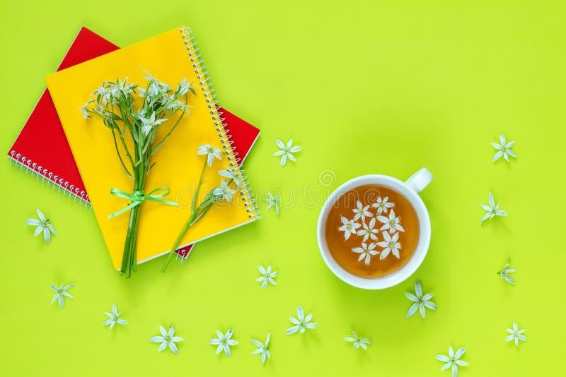 Φλυτζάνι του τσαγιού με τα άσπρα λουλούδια στη βεραμάν επιφάνεια στοκ φωτογραφία με δικαίωμα ελεύθερης χρήσης