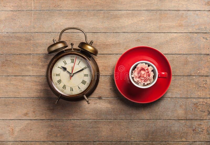 Φλυτζάνι του τσαγιού με το μπουμπούκι τριαντάφυλλου σε το και το ξυπνητήρι στοκ εικόνες