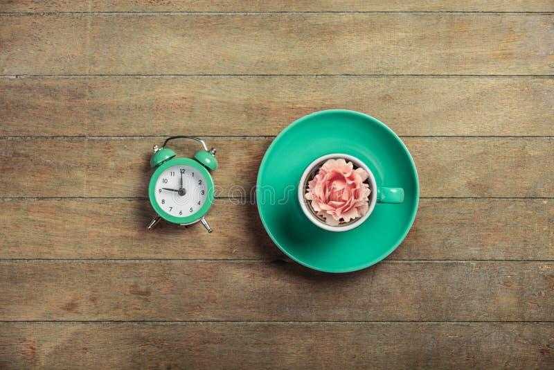 Φλυτζάνι του τσαγιού με το μπουμπούκι τριαντάφυλλου σε το και το ξυπνητήρι στοκ φωτογραφία με δικαίωμα ελεύθερης χρήσης