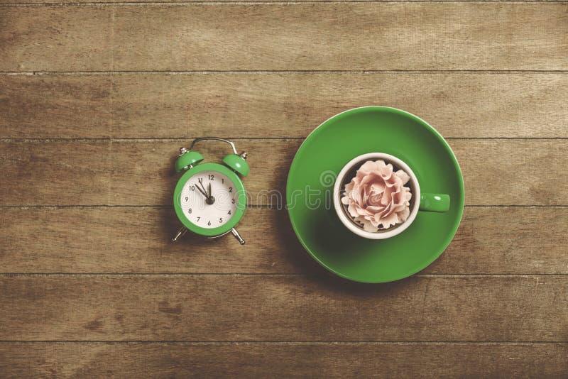 Φλυτζάνι του τσαγιού με το μπουμπούκι τριαντάφυλλου σε το και το ξυπνητήρι στοκ φωτογραφία