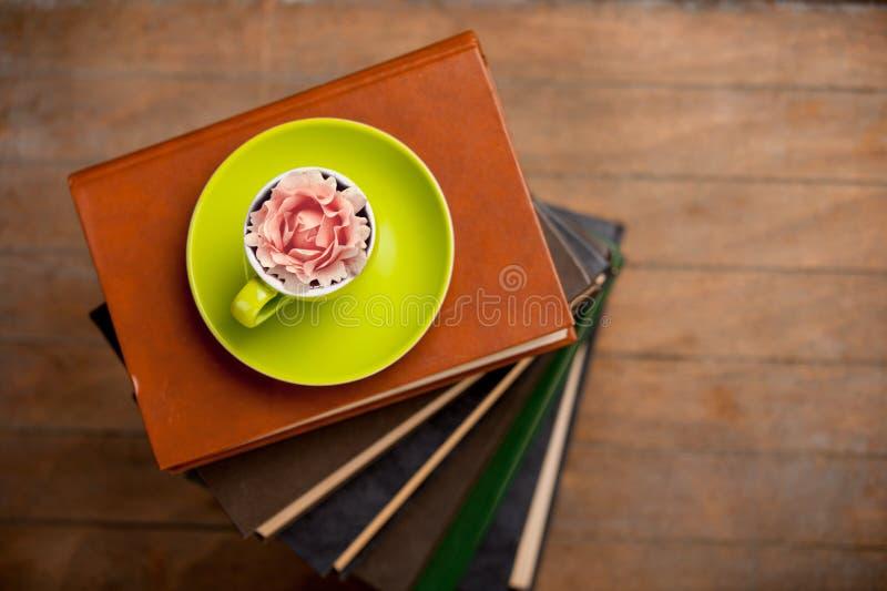 Φλυτζάνι του τσαγιού με το μπουμπούκι τριαντάφυλλου σε το και σωρός των βιβλίων στοκ εικόνες