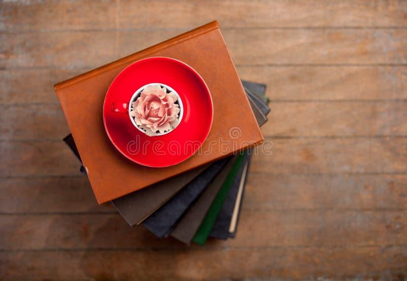 Φλυτζάνι του τσαγιού με το μπουμπούκι τριαντάφυλλου σε το και σωρός των βιβλίων στοκ εικόνες με δικαίωμα ελεύθερης χρήσης