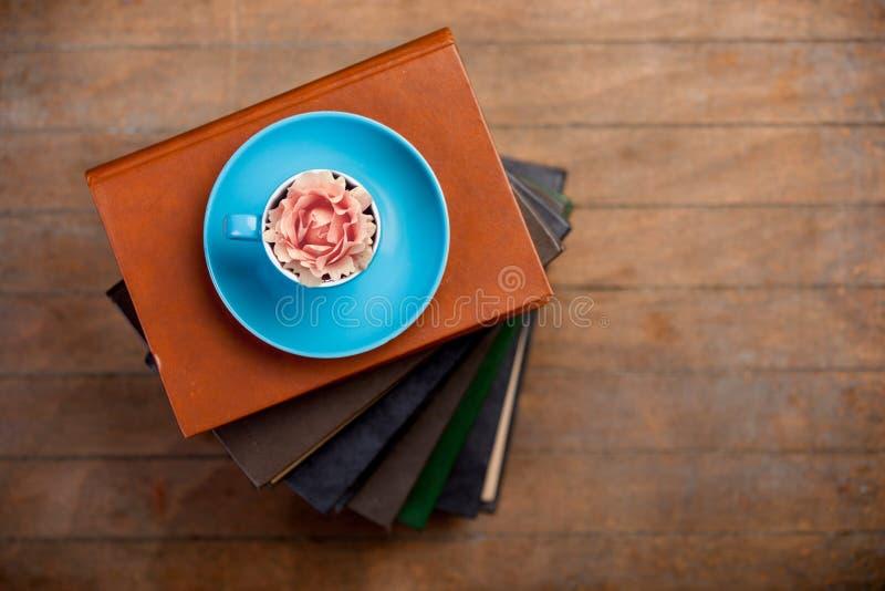 Φλυτζάνι του τσαγιού με το μπουμπούκι τριαντάφυλλου σε το και σωρός των βιβλίων στοκ εικόνα με δικαίωμα ελεύθερης χρήσης