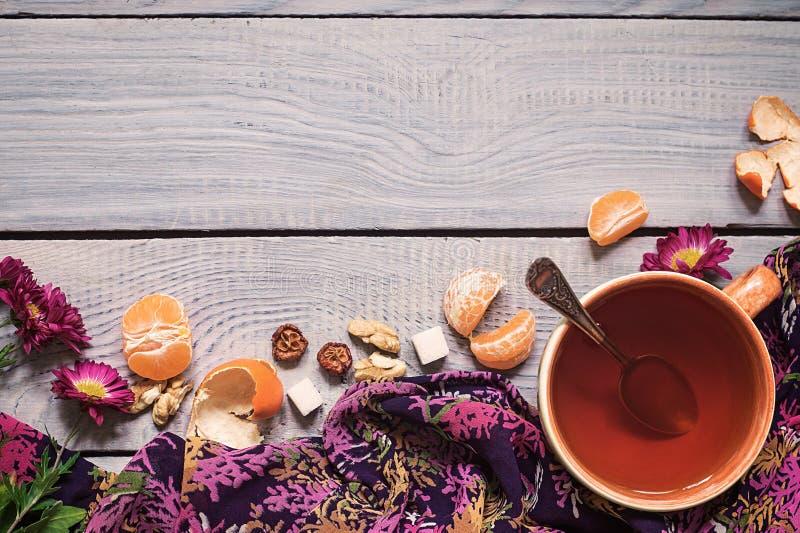Φλυτζάνι του τσαγιού, των λουλουδιών και tangerine σε έναν άσπρο ξύλινο πίνακα στοκ εικόνες