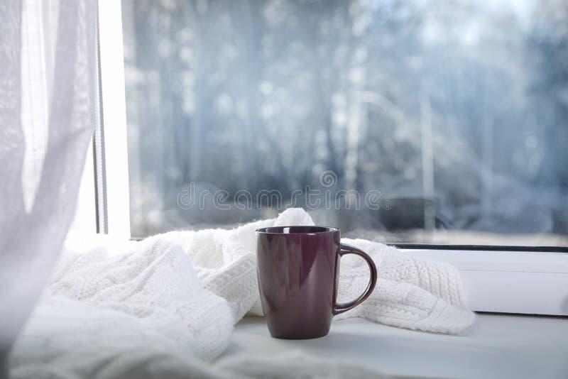 Φλυτζάνι του χειμερινού ποτού και του πλεκτού μαντίλι στο windowsill στοκ φωτογραφίες